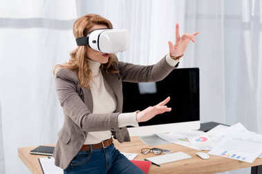 businesswoman in virtual reality headset at workplace in office