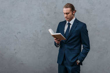 young serious businessman reading book in front of concrete wall