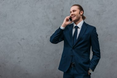 young happy businessman talking by phone in front of concrete wall
