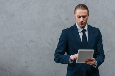 young serious businessman using tablet in front of concrete wall