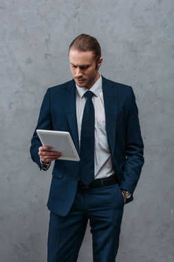 young handsome businessman using tablet in front of concrete wall