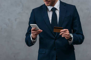 cropped shot of businessman with credit card and smartphone making e-shopping