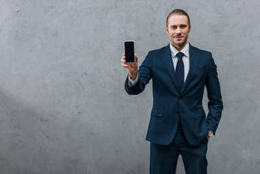 young handsome businessman showing smartphone at camera