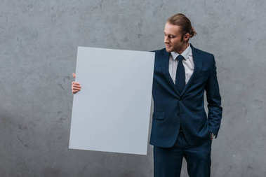 young stylish businessman holding blank board in front of concrete wall