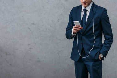 cropped shot of businessman listening music with headphones and smartphone