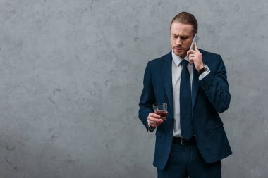 young serious businessman with glass of whiskey talking by phone