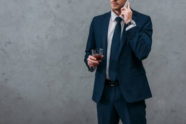 cropped shot of businessman with glass of whiskey talking by phone