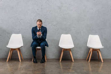 lonely businessman sitting on chair and using phone, phone addiction concept
