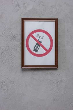 restricted phone placard on concrete wall