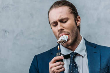 cropped shot of businessman with mouth full of cigarettes trying to smoke it