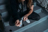Fotografie cropped shot of addicted junkie filling syringe with heroin from spoon