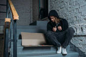 Fotografie hooded heroin addicted junkie sitting on stairs with syringes on cardboard