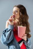 vonzó szexi lány, elszigetelt szürke pattogatott kukoricát eszik vörös ajkak