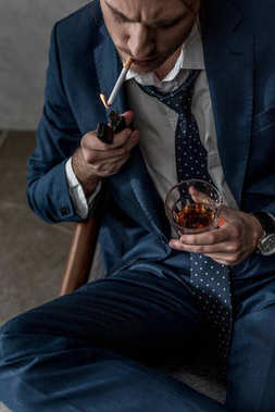 high angle view of businessman with glass of whiskey smoking cigarette