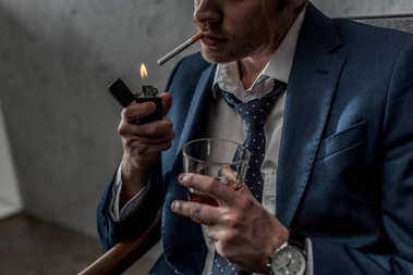 cropped shot of businessman with glass of whiskey smoking cigarette