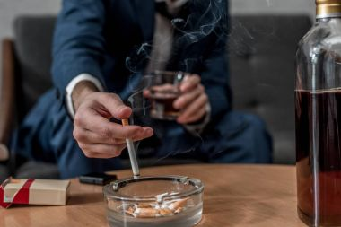 cropped shot of businessman with glass of whiskey and cigarette
