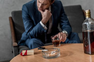 drunk depressed businessman with glass of whiskey