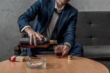 cropped shot of alcohol addicted businessman drinking whiskey while sitting on couch