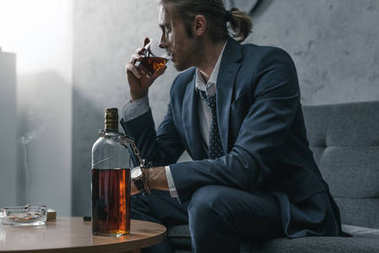 alcohol addicted businessman with glass and bottle of whiskey sitting on couch