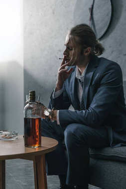 alcohol addicted businessman with glass and bottle of whiskey smoking cigarette