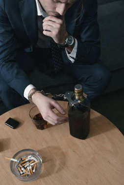 alcohol addicted businessman with glass and bottle of whiskey