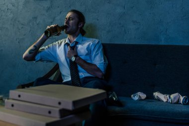 young alcohol addicted man drinking beer with pizza on couch after work