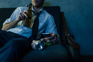 cropped shot of alcohol addicted man in white shirt watching tv and drinking beer after work
