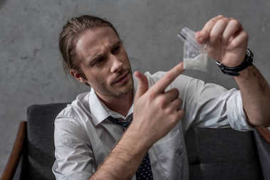 businessman with drug addiction holding pack of cocaine