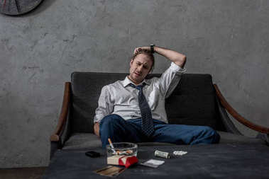 depressed businessman with drug addiction sitting on couch in front of table with drugs