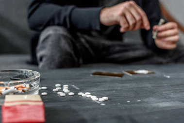 cropped shot of addicted man with various drugs on table