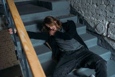 addicted junkie lying on stairs after taking dose