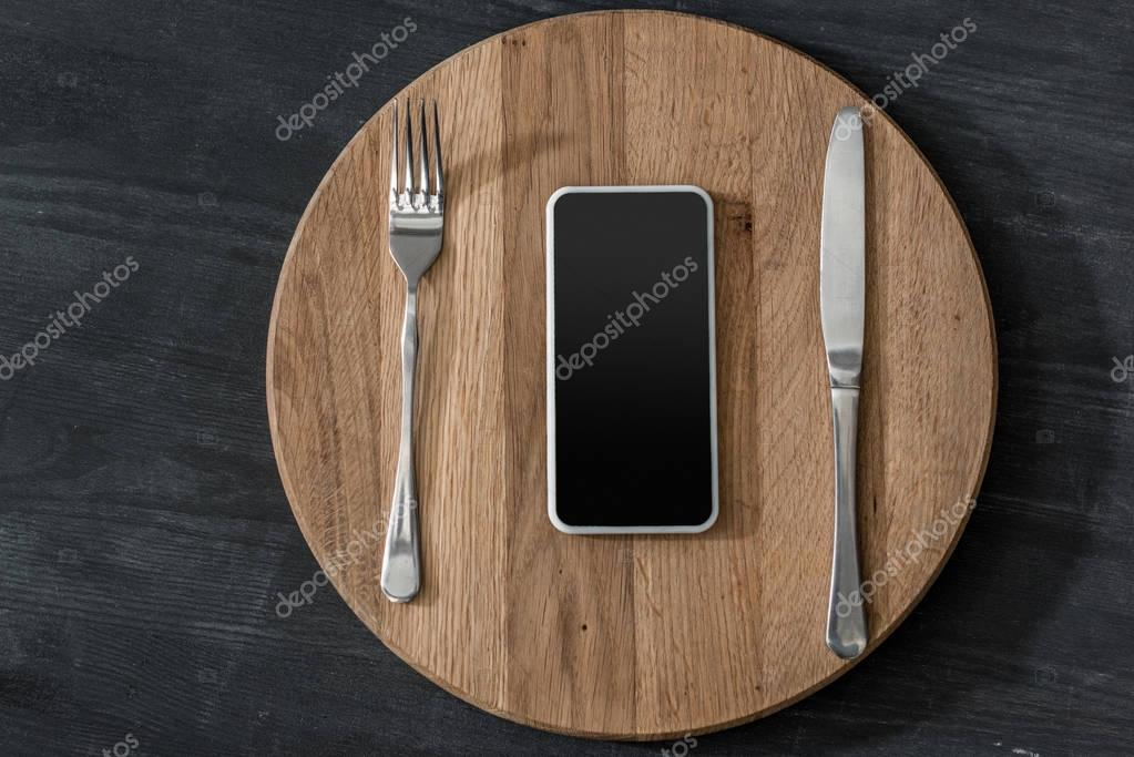 top view of smartphone lying on wooden board with cutlery, phone addiction concept