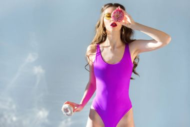 sexy attractive girl in ultra violet swimsuit covering eye with donut on grey