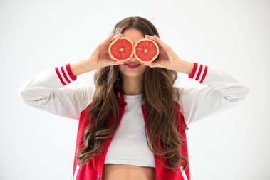 sexy girl in baseball jacket covering eyes with grapefruit pieces isolated on white