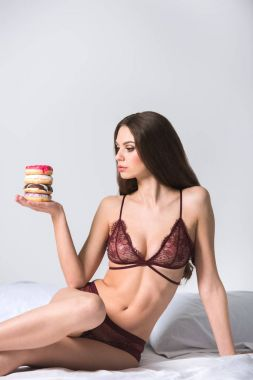 seductive woman sitting on bed in lace lingerie and holding doughnuts