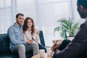 Usměvavý mladý pár sedí na pohovce a mluví poradce s tužkou v ruce