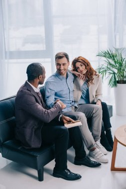 Psychotherapist shaking hand of young man and woman sitting near