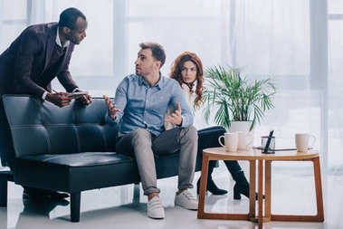 Counselor with clipboard talking to upset couple sitting on couch