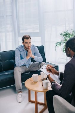 Young man sitting on couch and talking to african american counselor