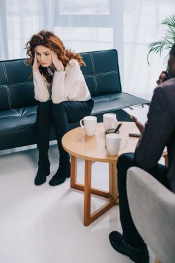 Upset woman sitting on couch and psychiatrist sitting near