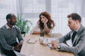 Finanční poradce dělá výpočet při obchodních partnerů u stolu