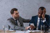 Fiatal stílusos üzletember ujjongott fel ideges partner smartphone a kezében