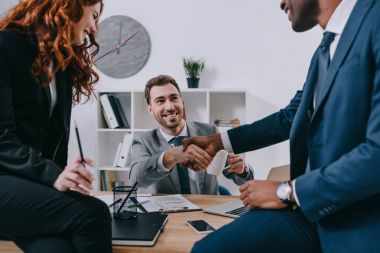 Three businesspeople having meeting in modern office stock vector