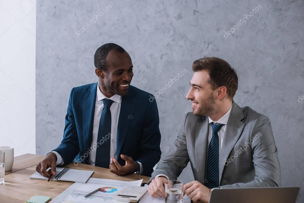 Multiethnic businessmen working at table with papers and laptop stock vector