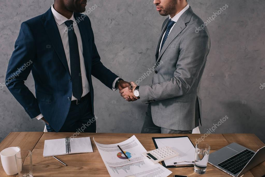 Cropped view of two businessmen shaking hands of each other stock vector