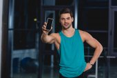 Photo handsome sportsman showing smartphone with blank screen