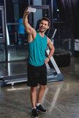Fotografie fröhliche Sportler nehmen Selfie auf Smartphone im Fitnessraum mit Laufband
