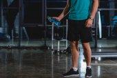 Fotografie oříznutý pohled sportovce drží sportovní láhev ve sportovní hale