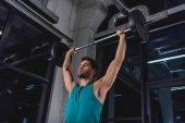 Fotografie silné sportovec zvedání činka během cross trénink v tělocvičně