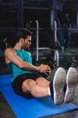 Fotografia allenamento con palla medica sulla stuoia di yoga nel centro sportivo sportivo